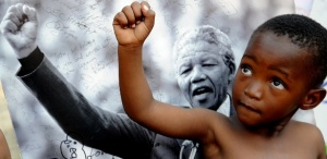 apartheid---crianca-posa-para-foto-em-frente-a-imagem-de-nelson-mandela-1374004048574_615x300